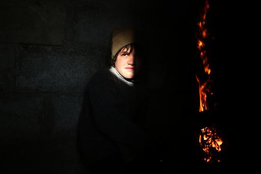 A boy stands near a fire in the rebel held besieged Douma neighbourhood of Damascus