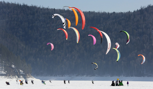 Kite boarders and kite skiers compete during a regional snow kiting championship outside Krasnoyarsk