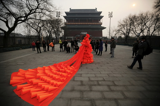 Chinese artist Kong Ning walks in her costume made of hundreds of orange plastic blowing horns during her art performance raising awareness of the hazardous smog in front of the Drum tower in a historical part of Beijing