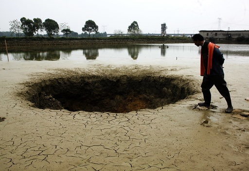 A man looks into a sinkhole which appeared in his fish pond in Guiping