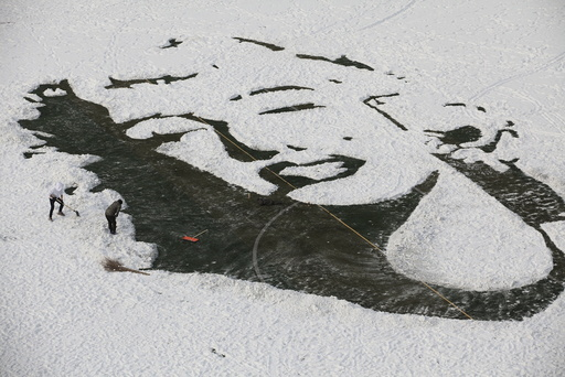 University students create an image of Marilyn Monroe by clearing snow on a soccer pitch, in Changchun