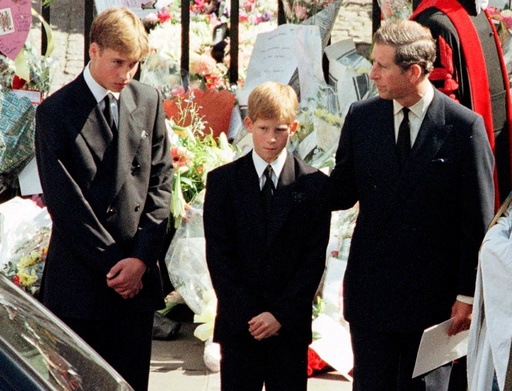 Prince Charles touches the shoulder of his son Harry as his other son Prince William watches the hea..