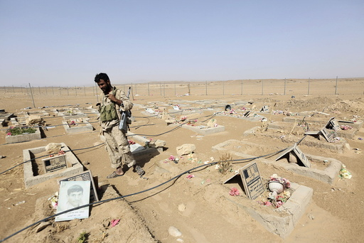 An army soldier stands next to graves of Houthi fighters in the historical town of Baraqish in Yemen's al-Jawf province