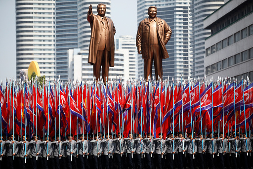 People carry flags in front of statues of North Korea founder Kim Il Sung and late leader Kim Jong Il during a military parade marking the 105th birth anniversary Kim Il Sung in Pyongyang