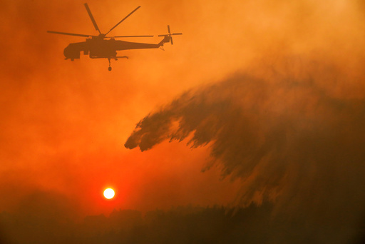 A firefighting helicopter makes water drop as a wildfire burns near the village of Metochi
