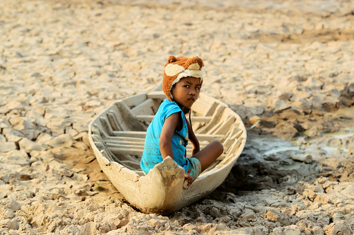 A girl sits on her boat at a Bak Angrout dried up pond at the drought-hit Kandal province in Cambodia