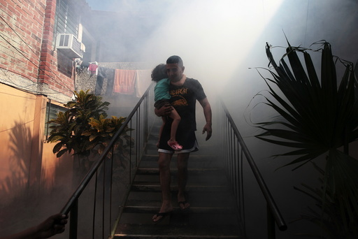 A man walks away from his home with his son as health workers fumigates the Altos del Cerro neighbourhood as part of preventive measures against the Zika virus and other mosquito-borne diseases in Soyapango, El Salvador