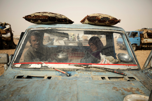 Internally displaced people who fled Raqqa city ride a vehicle in a camp near Ain Issa