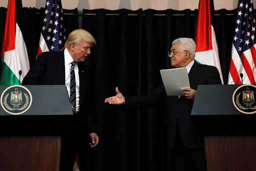 Abbas extends his hand to Trump during their remarks after their meeting at the Presidential Palace in the West Bank city of Bethlehem