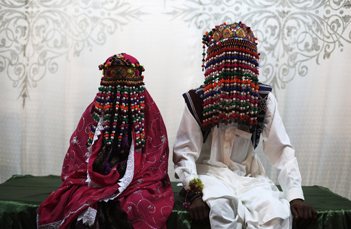A bride and groom wearing traditional garlands wait for their wedding to start during a mass marriage ceremony in Karachi