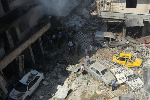 Residents inspect a damaged site after airstrikes on a market in the rebel controlled city of Idlib