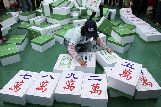 A woman participates in a giant mahjong game in Kunming