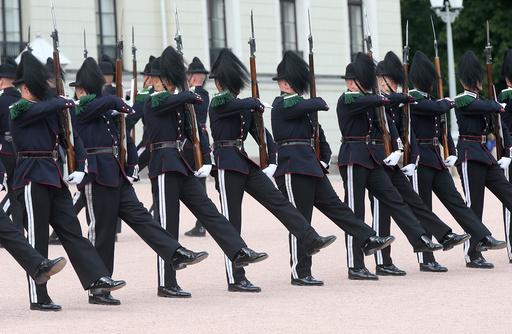 Dronning Sonja og Kong Harald overværer Gardens drilloppvisning på Slottsplassen fra Slottsbalkongen.