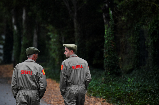 Two visitors dressed in 'Shell' emblazoned mechanics uniforms walk at the annual Goodwood Revival historic motor racing festival, celebrating a mid-twentieth century heyday of the racing circuit, near Chichester in south England