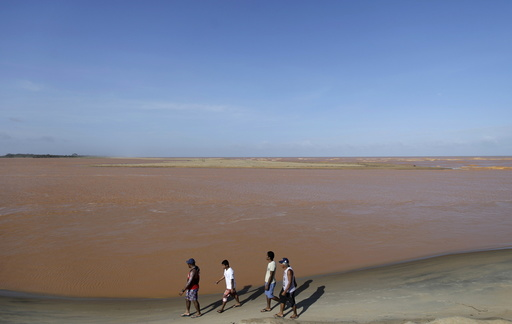 Men walk on the banks of the mouth of Rio Doce, which was flooded with mud after a dam owned by Vale SA and BHP Billiton Ltd burst, as the river joins the sea on the coast of Espirito Santo, in Regencia Village, Brazil