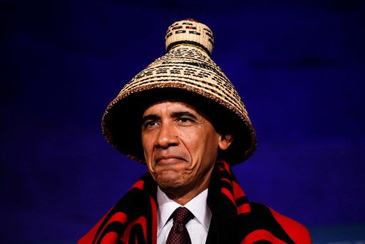 U.S. President Barack Obama looks up as is honored in a blanketing ceremony before speaking at the White House Tribal Nations Conference in Washington