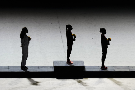 From left, silver medalist Brigid Kosgei, of Kenya, gold medalist Peres Jepchirchir, of Kenya, and bronze medalist Molly Seidel of, the United States, stand on the podium after receiving medals for the women's marathon during the closing ceremony in the Olympic Stadium at the 2020 Summer Olympics, Sunday, Aug. 8, 2021, in Tokyo, Japan. (AP Photo/Vincent Thian)