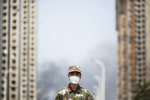 A paramilitary policeman wears a mask as he blocks the road leading to evacuated residential area and the explosion site in Binhai new district in Tianjin