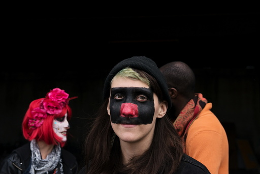 A woman with face paint poses for a photograph during