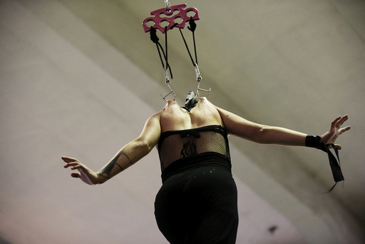 A woman hangs on hooks pierced into her skin during the latin america convention of tattoo and suspension in Valparaiso city
