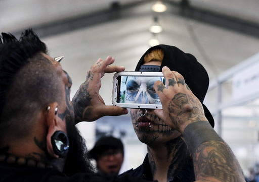 Venezuelan tattoo artist and body modifier Emilio Gonzalez takes a picture of the eyeball tattoo on Eduardo Henriquez of Chile during the latin america convention of tattoo and suspension in Valparaiso city