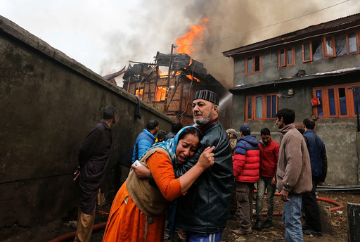 A woman is consoled by her relative as she mourns after seeing her house getting burned during a fire that broke out in a residential locality in Srinagar