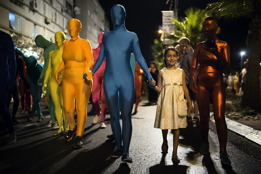 A group of people wearing full solid-coloured bodysuits walk along a promenade as they take part in a street art performance in Bat Yam, near Tel Aviv, Israel