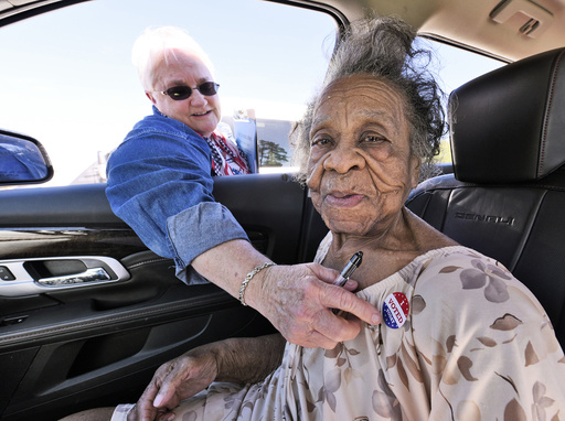100 year old Grace Bell Hardison receives an I Voted Today sticker from election official Elain