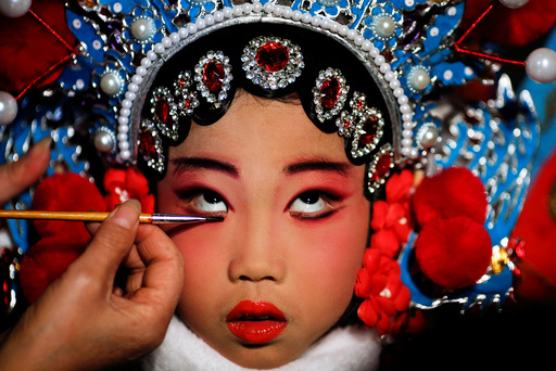 A participant has her make-up done during a traditional Chinese opera competition at the National Academy of Chinese Theatre Arts in Beijing