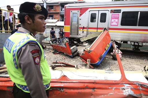 A police officer stands near the scene of an accident between a minibus and a commuter train at a railway crossing in West Jakarta