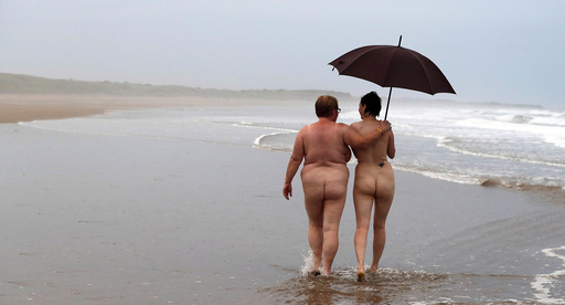 Two women walk along the beach after taking part in the annual North East Skinny Dip at Druridge Bay
