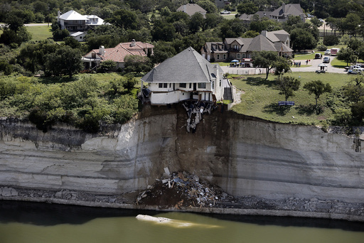 Crews prepare to set a house on fire, days after part of the ground it was resting on collapsed into Lake Whitney