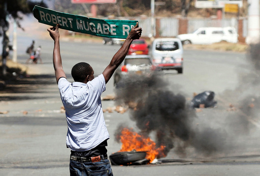 A man carries a street sign as opposition party supporters clash with police in Harare