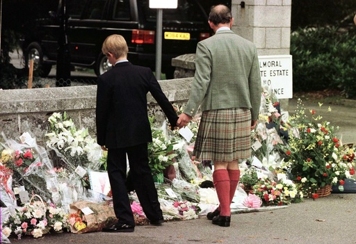 Prince Charles (R) holds Prince Harry's hand as they view the floral tribute on display outside the ..