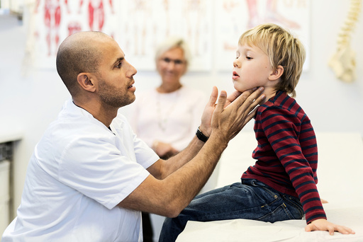 Side view of male doctor checking boy's throat at clinic
