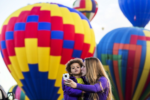 A woman and child take a photograph as hot air balloons lift off during the 2015 Albuquerque International Balloon Fiesta in Albuquerque, New Mexico