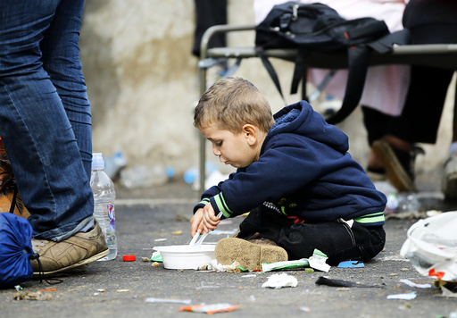 A migrant boy eats on the ground at the check point Heiligenkreuz