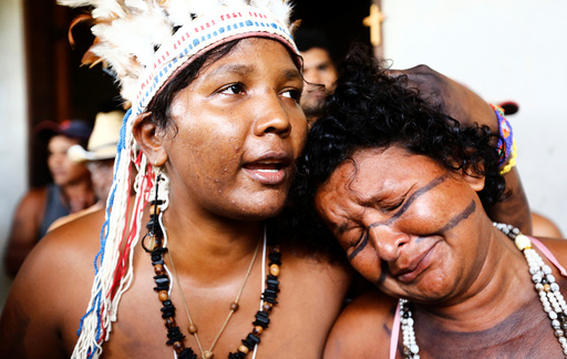 Preta and Gabao from Brazil's indigenous Gamela tribe react after members of their tribe were injured in a dispute over land in northern Brazil