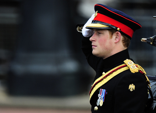 Britain's Prince Harry salutes as he leaves Buckingham Palace to attend the Trooping the Colour ceremony in London