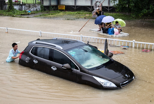 A trapped car is pushed along a flooded street after typhoon Soudelor hit Fuzhou
