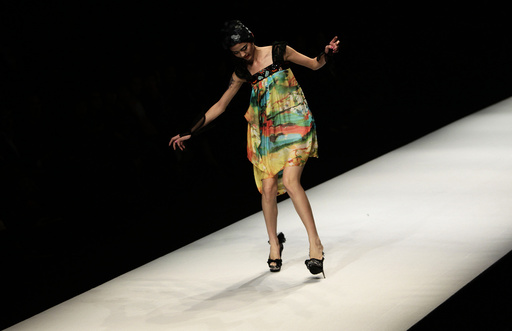 A model nearly falls as she presents a creation at China Fashion Week in Beijing