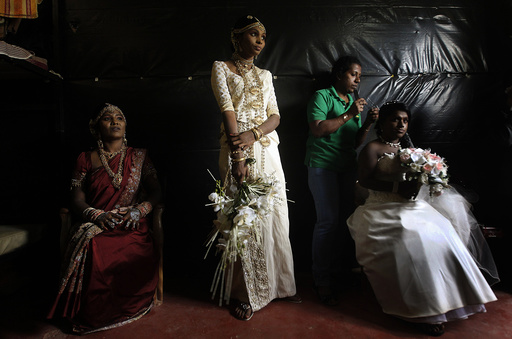 Former LTTE female rebel fighters and brides look on as an ethnic Tamil gets ready before the start of a mass wedding in Kilinochchi