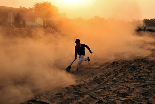 A boy plays with a makeshift wheel outside his house on a dusty road in Jammu