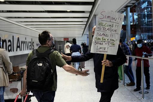 En mann holder et humoristisk skilt for å ønske broren sin velkommen på Heathrow lufthavn mandag. Foto: Matt Dunham / AP / NTB
