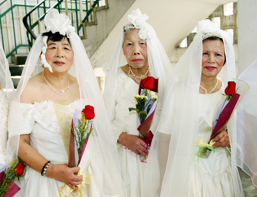 ELDERLY WOMEN RECEIVE FLOWERS AT A VALENTINE'S DAY CEREMONY IN HONG KONG