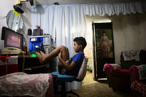 A boy watches a recorded TV show through the screen of a computer at the living room of his home in downtown Havana