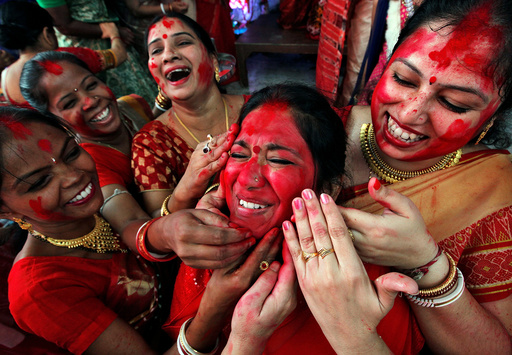 Hindu women apply sindhur, or vermillion powder, on the face of a woman after worshipping the idol of the Hindu goddess Durga on the last day of the Durga Puja festival in Chandigarh
