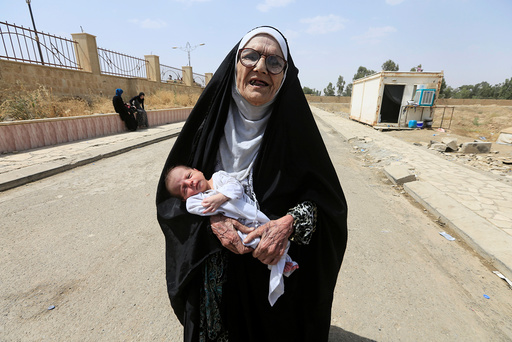 An elderly displaced Iraqi woman who fled from Islamic State militants carries a baby in Mosul