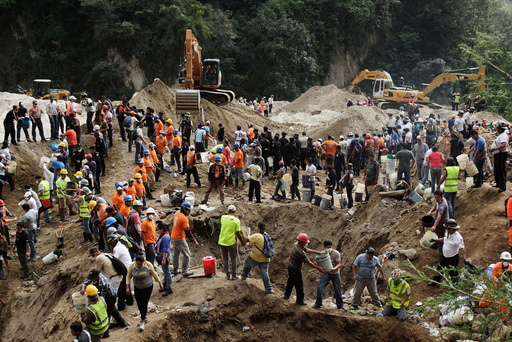 Rescue team members and volunteers remove dirt with buckets from the site of a mudslide in Santa Catarina Pinula