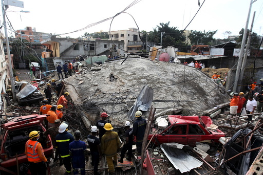 Emergency services workers search a house that collapsed after explosions at an LPG gas distribution station in Santo Domingo, Dominican Republic